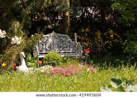 Shaded area with beautiful old garden bench in a beautiful garden - stock photo