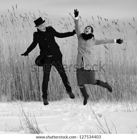 Shaded man and woman jump on lake beach