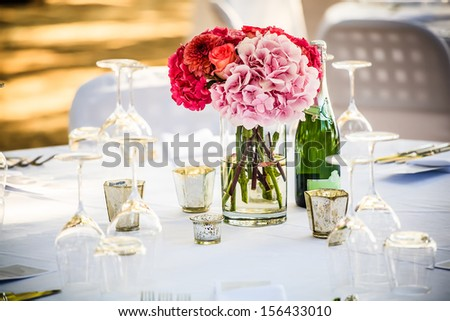 shades of pink hydrangea centerpiece placed on a crisp white decorated table - stock photo