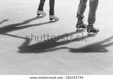 shadow background of group of teenagers on the ice holding hands at the Medeo - stock photo