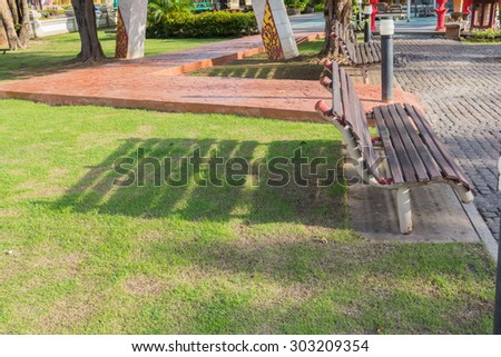 shadow bench wood on green grass evening time