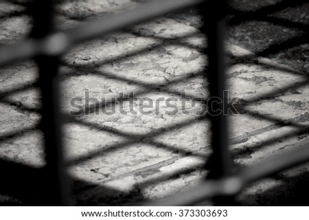 shadow from bars of an abandoned building in Verona, Italy,