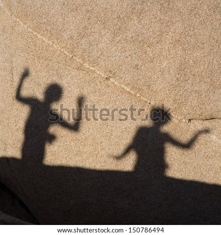 shadow game of children with Scenic rocks  in Joshua tree national park, they play with shadow at the rock by using their arms and hands - stock photo