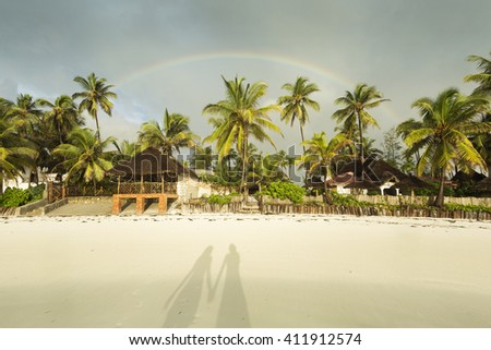 Shadow of a couple on a sands with palm tree and rainbow in background - stock photo