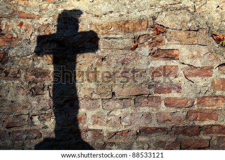 Shadow of a cross on a wall - stock photo