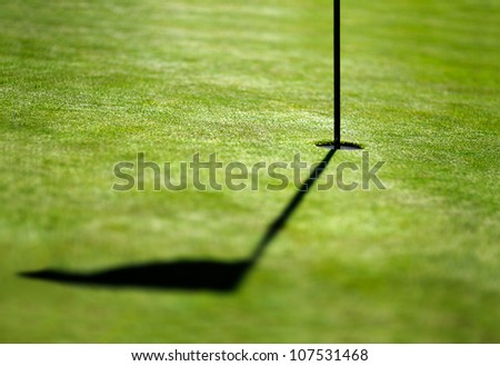 shadow of a flag on golf field - stock photo