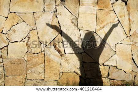 Shadow of a girl raising her hand over her head in celebration, on a grungy rubble wall.   - stock photo