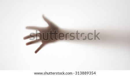 shadow of a hand behind transparent paper - stock photo