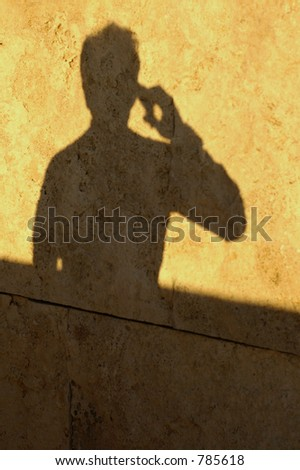 Shadow of a man talking on the phone - stock photo