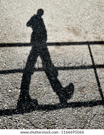 Shadow of a person balancing on a rail while walking on it reflected on a gravel ground