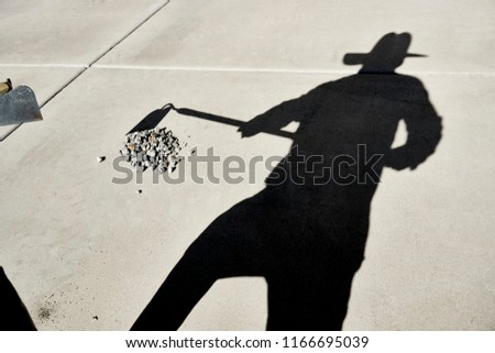 Shadow of a Person holding a Hoe to scoop gravel reflected on a cement slab