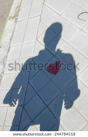 Shadow of a person with a heart painted on the floor - stock photo