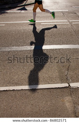 shadow of a runner in a marathon competition - stock photo