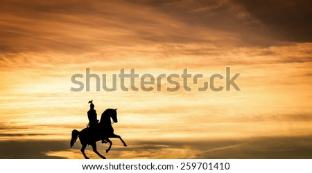 Shadow of a statue with a rider on a horse at sunset