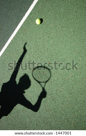 Shadow of a Tennis Player Serving - stock photo