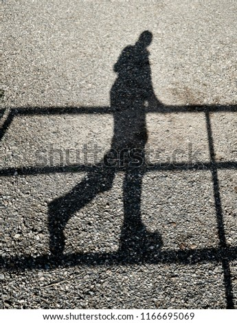 Shadow of a walking on a fence reflected on the gravel ground