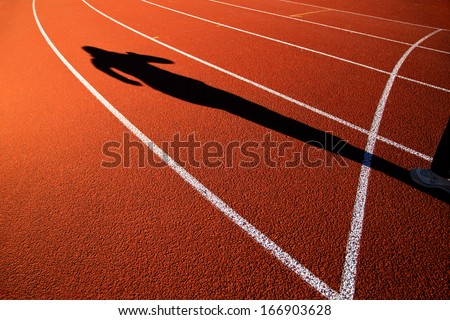 Shadow of athlete running on track. - stock photo