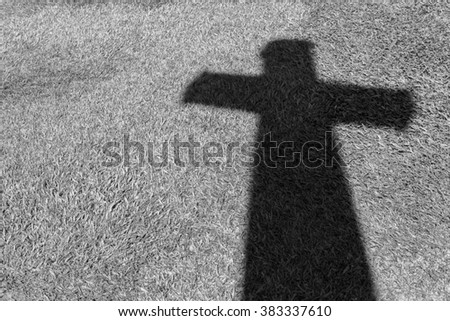 Shadow of Christian cross on green grass floor in Black and white style - stock photo