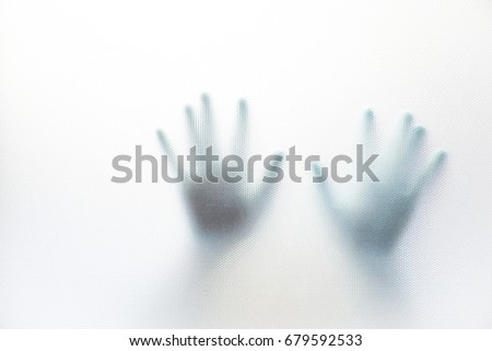 Shadow of hand behind the glass.