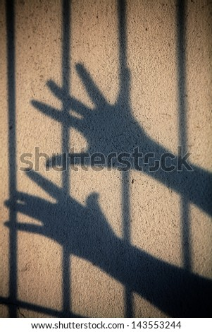 shadow of hand in jail. - stock photo