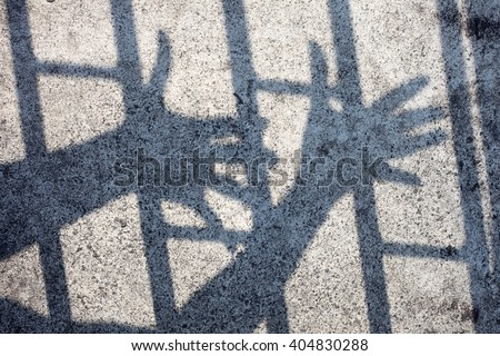 shadow of hand in jail - stock photo