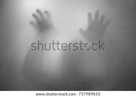 shadow of hands behind frosted glass