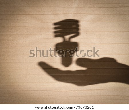 shadow of human hand holding shadow of fluorescent light bulb against cardboard background - stock photo