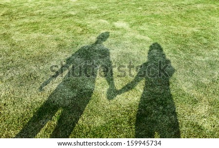 shadow of lover hand in hand in sunset - stock photo
