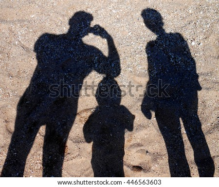 Shadow of mother and daughter walk on the beach over sand during summer vacation. Concept photo of: Mothers day, relationship, child care, childhood, motherhood.