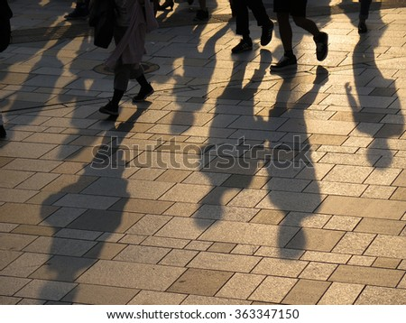 shadow of people walking together - stock photo