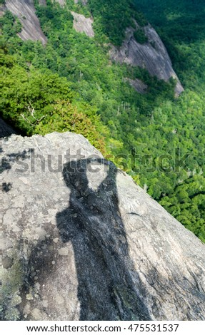 Shadow of photographer on Fools Rock at the summit of Whiteside Mountain near Highlands and Cashiers in North Carolina