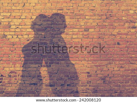 shadow of the man and the woman on dirty brick wall, retro film filtered, instagram style  - stock photo