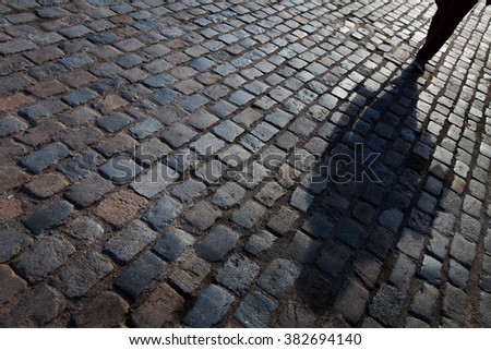 Shadow of the person on paving slabs - stock photo