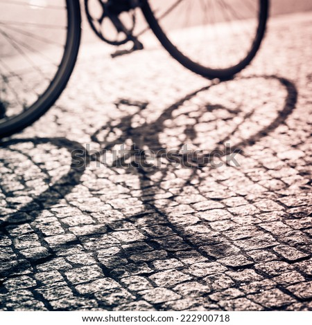 Shadow of the vintage bike in Berlin. Retro filtered. Monochrome cream tone. Black and white photography. - stock photo