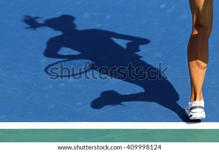 Shadow of woman tennis player, serving the ball - stock photo
