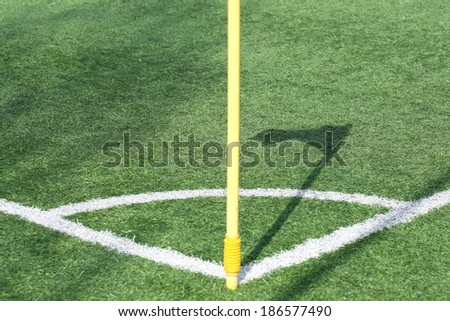shadow of yellow flag in the corner of a soccer field
