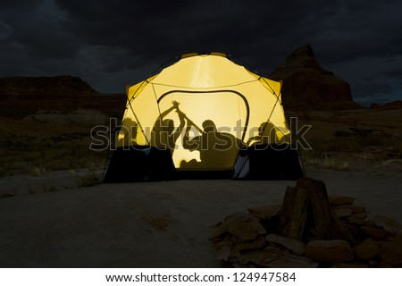 Shadow of young people sitting together in tent - stock photo