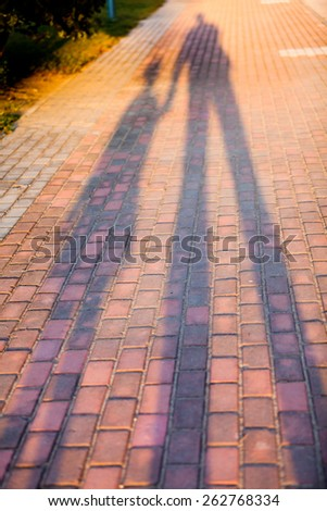 Shadow on path of a father and child. They holding hands - stock photo