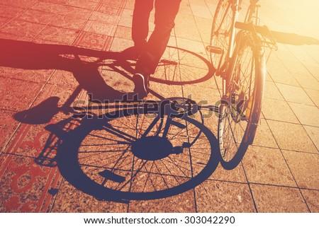 Shadow on Pavement, Man Pushing Bicycle on the Street, Urban Setting, Retro Toned Image - stock photo