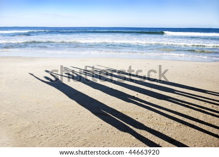 Shadow silhouettes of five people on the beach