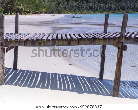 Shadows are cast from a wooden pier or jetty on Ao Phrao Beach on Ko Kut island, east Thailand