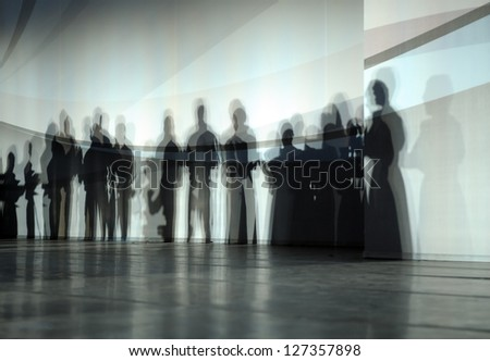 Shadows of group of standing people. - stock photo