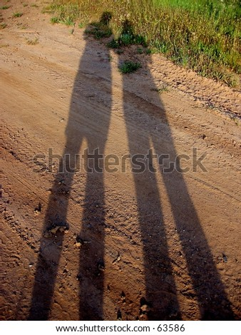 Shadows of 2 people on a country road - stock photo
