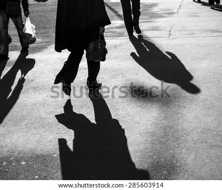 Shadows of people walking in a street in morning light - stock photo