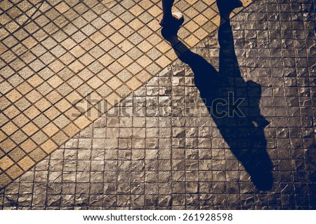 Shadows of people walking in a street in the city - stock photo