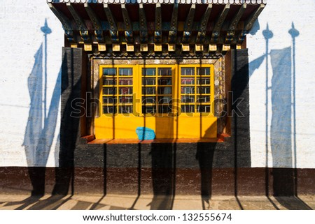Shadows of prayer flags against the colorful windows and wall of the Pemayagtse buddhist monastery in Pelling, Sikkim, India - stock photo