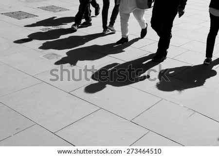 Shadows of six walking pedestrians projected on the sidewalk. Black and white. - stock photo