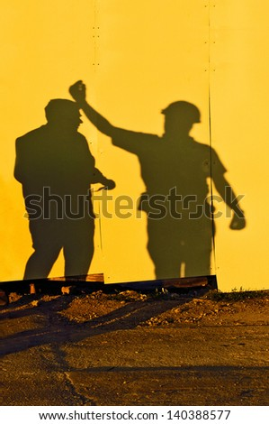Shadows of two male figures construction workers on construction site.