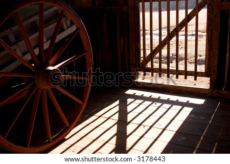 shadows on a barn floor with wagon wheel