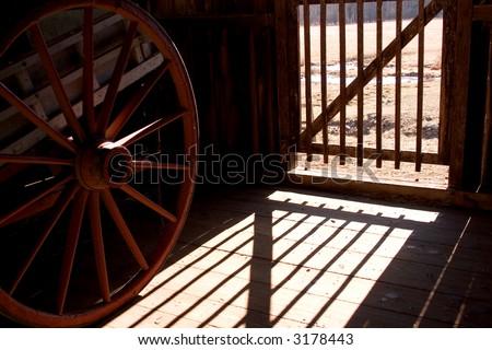 shadows on a barn floor with wagon wheel - stock photo